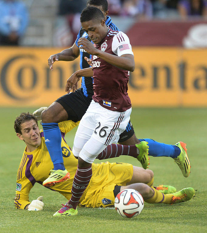 . Colorado forward Deshorn Brown (26) tried to get around Montreal goalkeeper Troy Perkins in the first half. The Colorado Rapids hosted the Montreal Impact Saturday night, May 24, 2014. (Photo by Karl Gehring/The Denver Post)