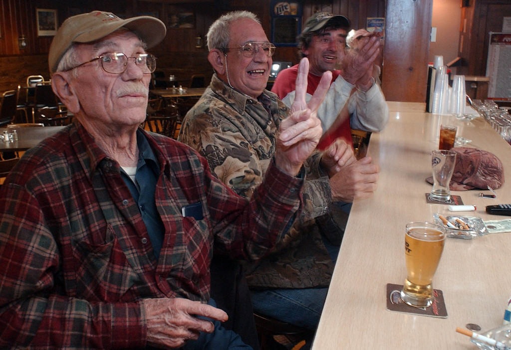 . Boston Red Sox fans, from left, Cliff Morton, Bob Sacco and Chris Lashway celebrate after the Red Sox scored two runs in the third inning against the St. Louis Cardinals, as they watch Game 4 of the World Series on television at VFW Post 754 in Amherst, Mass. Wednesday night, Oct. 27, 2004. (AP Photo/Nathan K. Martin)