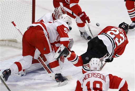 . Chicago Blackhawks right wing Kris Versteeg (23) takes a shot on goal as Detroit Red Wings defenseman Niklas Kronwall (55) and Jimmy Howard defend during the first period of an NHL hockey game Wednesday, Feb. 18, 2015, in Chicago. (AP Photo/Charles Rex Arbogast)