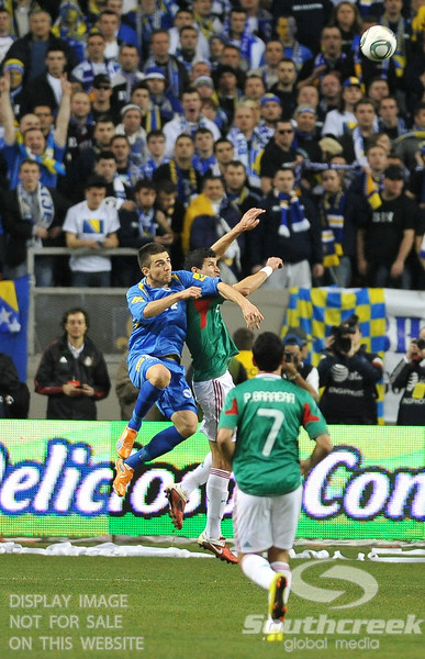 Bosnia-Herzegovina's Defencer Emir Spahic (#4) goes after the ball during Soccer action between Bosnia-Herzegovina and Mexico.  Mexico defeated Bosnia-Herzegovina 2-0 in the game at the Georgia Dome in Atlanta, GA.