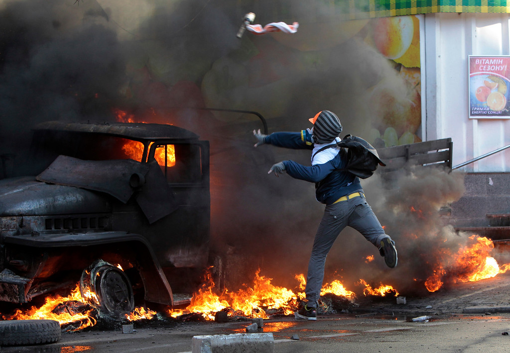 . An anti-government protester throws a Molotov\'s cocktail during clashes with riot police outside Ukraine\'s parliament in Kiev, Ukraine, Tuesday, Feb. 18, 2014.  (AP Photo/Sergei Chuzavkov)