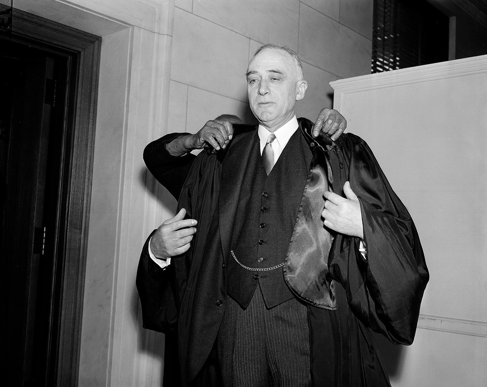 . Judge John Marshall Harlan II, new Associate Justice of the Supreme Court, appears to have four hands as he puts on his robes in Washington, D.C., March 28, 1955. Actually, the upper pair belong to Robert Marshall, custodian of the court\'s robing room, a short man whose head is partially visible above the judge\'s shoulder. (AP Photo/William J. Smith)