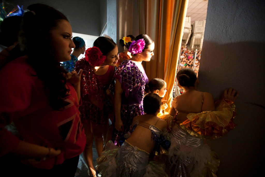 ". In this Jan. 26, 2013 photo, dancers watch from backstage as young women compete in the ""Guamuchil Carnival Queen 2013\"" beauty contest in Guamuchil, Sinaloa state, Mexico. Residents packed the local theater filled with banners and posters advertising the queens and filled the aisles and stairways with extra chairs after the seats filled. The town has produced at least a Miss Mexico and more recently prides itself in saying the runner up to Miss World 2009 is a native. (AP Photo/Eduardo Verdugo)"
