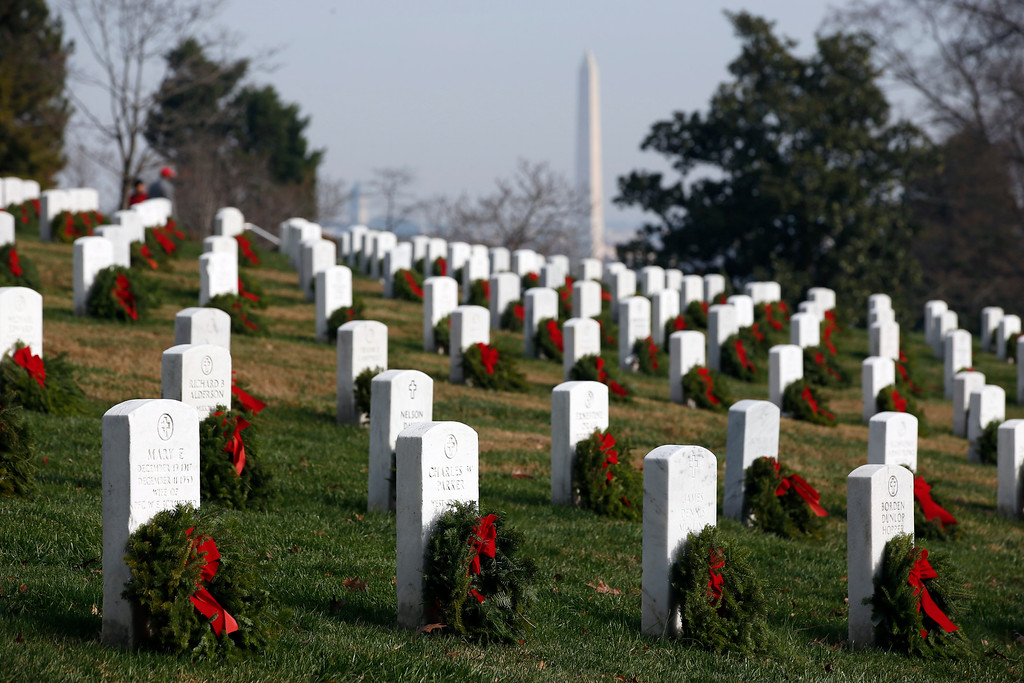 . The Washington Monument is seen behind the graves after wreaths were placed in front of them as part of Wreaths Across America at Arlington National Cemetery, Saturday, Dec. 12, 2015 in Arlington, Va. Organizers estimated that volunteers placed 240,815 wreaths at Arlington. (AP Photo/Alex Brandon)