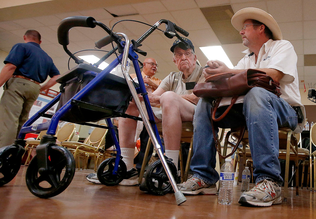 . VA SCANDAL: In this June 10, 2014 file photo, Don Parker, right, sits with his father, Harley Parker, center, a World War II veteran, as they wait to speak with someone at a health care crisis center set up by the American Legion at the American Legion Post 1 hall in Phoenix. The FBI revealed on Wednesday, June 11, that it had opened a criminal investigation into a Department of Veterans Affairs reeling from allegations of falsified records and inappropriate scheduling practices. (AP Photo/Ross D. Franklin, File)