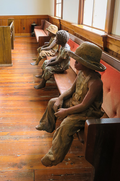 statues of children sitting on a long bench