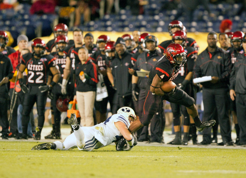 . Adam Muema #4 of the San Diego State Aztecs runs with the ball in the first half of the game as Brandon Ogletree #44 of the BYU Cougars attepts a tackle in the Poinsettia Bowl at Qualcomm Stadium on December 20, 2012 in San Diego, California. (Photo by Kent C. Horner/Getty Images)