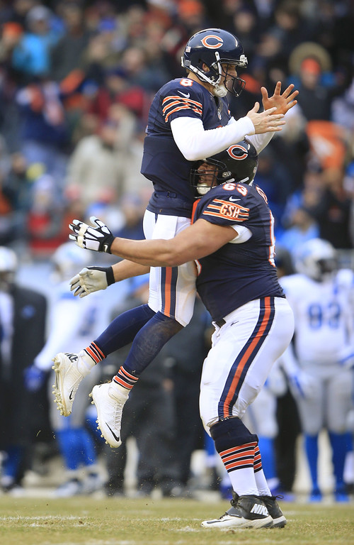. CHICAGO, IL - DECEMBER 21: Jimmy Clausen #8 of the Chicago Bears gets a lift from Roberto Garza #63 after a touchdown during the second quarter of a game against the Detroit Lions at Soldier Field on December 21, 2014 in Chicago, Illinois. (Photo by Jamie Squire/Getty Images)