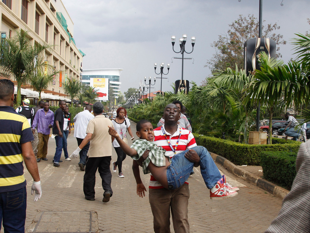 . A rescue worker helps a child outside the Westgate Mall in Nairobi, Kenya Saturday, Sept. 21, 2013, after gunmen threw grenades and opened fire during an attack that left multiple dead and dozens wounded.  (AP Photo/Khalil Senosi)