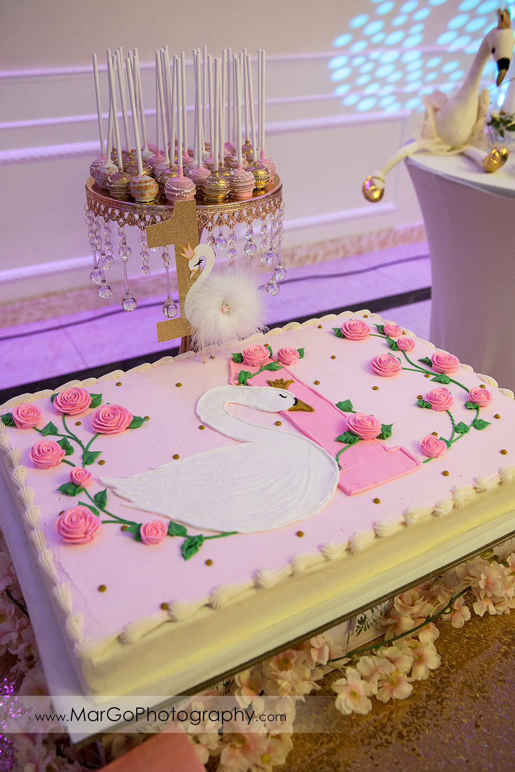 first birthday pink cake decorated with white swan and pink roses at Newark Oasis Palace