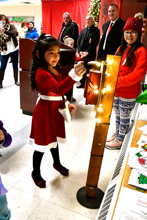 12/13/2019 Mike Orazzi | Staff Wheeler Elementary School student Brittany Gutierrez, 6 1/2, flips the switch while waiting for Santa to arrive at the Plainville Fire Company for the town tree lighting ceremony on Friday evening.
