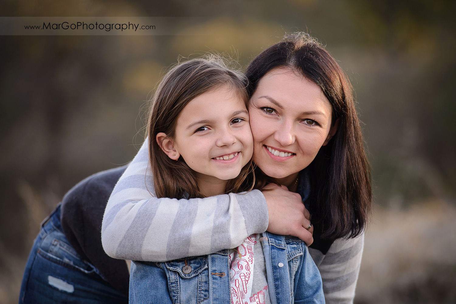 horizontal portrait of mother and daugher wearing blue and grey clothes and looking into camera during family session at Old Borges Ranch in Walnut Creek