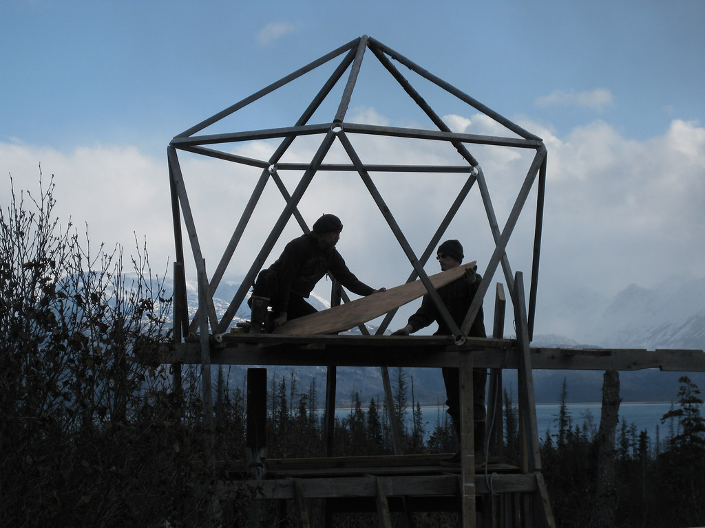 . Bill & Jake add plywood flooring to the top of the icosahedron section; the men are working within the silver structure, and mountains are far off in the distance.  Provided by Discovery Channel