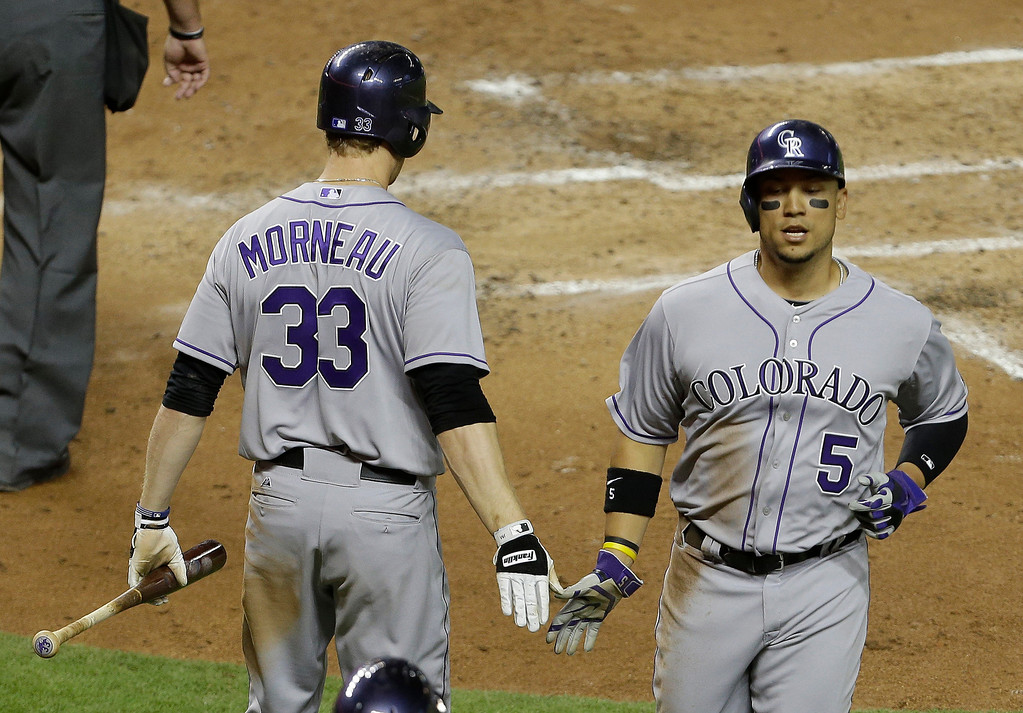 . Colorado Rockies\' Carlos Gonzalez (5) is met by Justin Morneau (33) after scoring on a double by Troy Tulowitzki in the fourth inning of an MLB National League baseball game against the Miami Marlins, Tuesday, April 1, 2014, in Miami. (AP Photo/Lynne Sladky)