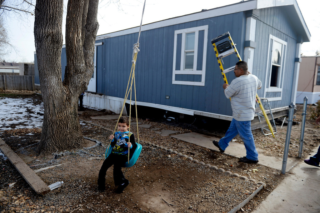 . MILLIKEN, CO - DECEMBER 18: Jorge Neveo carries a ladder into his sister Laura Medina\'s mobile home as neighbor Angelo Castillo, 3, swings. Residents of the mobile home park say that the city of Milliken has not done enough to assist in the rebuilding of the 33-unit residential sub division that was struck hard by recent floods that ravaged much of northern Colorado. (Photo by AAron Ontiveroz/The Denver Post)