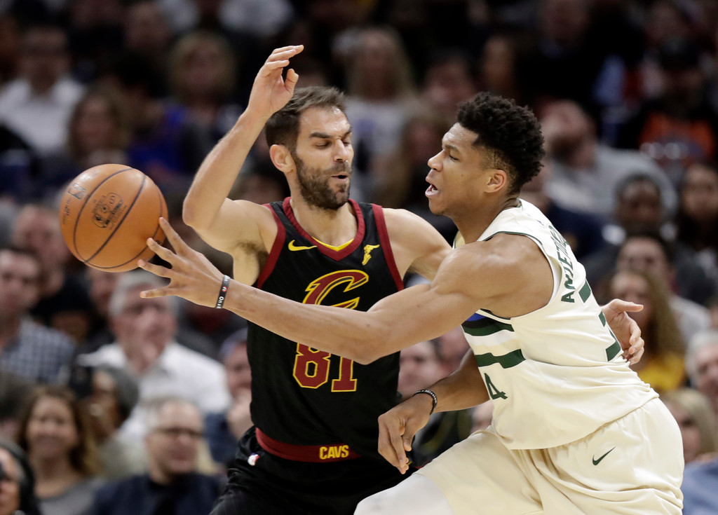 . Milwaukee Bucks\' Giannis Antetokounmpo (34), from Greece, passes around Cleveland Cavaliers\' Jose Calderon (81), from Spain, in the first half of an NBA basketball game, Monday, March 19, 2018, in Cleveland. (AP Photo/Tony Dejak)