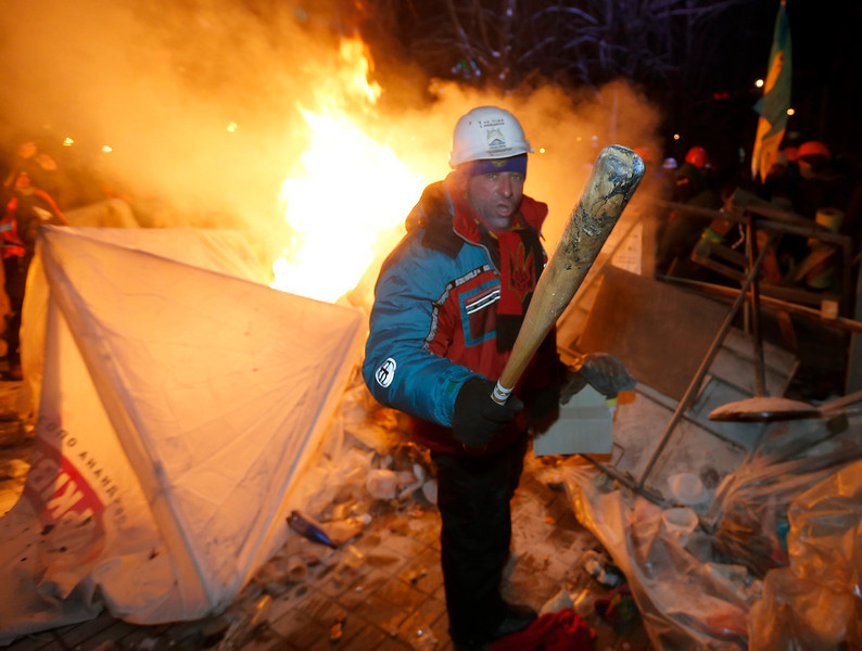 . An Ukrainian man stands near a burning tent as pro-EU protesters defend their barricades at Independence Square in Kiev, Ukraine, 11 December 2013. Ukrainian riot police reoccupied part of the square where thousands of pro-European protesters demand early elections and resist calls from police to vacate the central Independence Square.  EPA/SERGEY DOLZHENKO