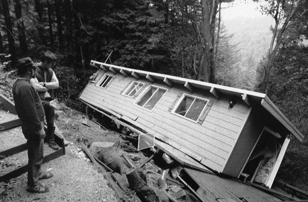. Bob Kubiatowicz, left, and John Wooliscroft look at whats left of a neighbors home, Friday, Oct. 21, 1989, Boulder Creek, Calif. Kubiatowiczs home was untouched while Wooliscrofts suffered the same fate as that pictured.  (AP Photo/Douglas C. Pizac)