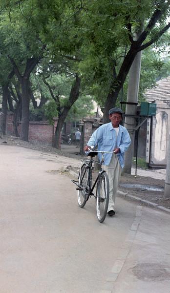 Man walking his bicycle, rural scene, China, 1990s