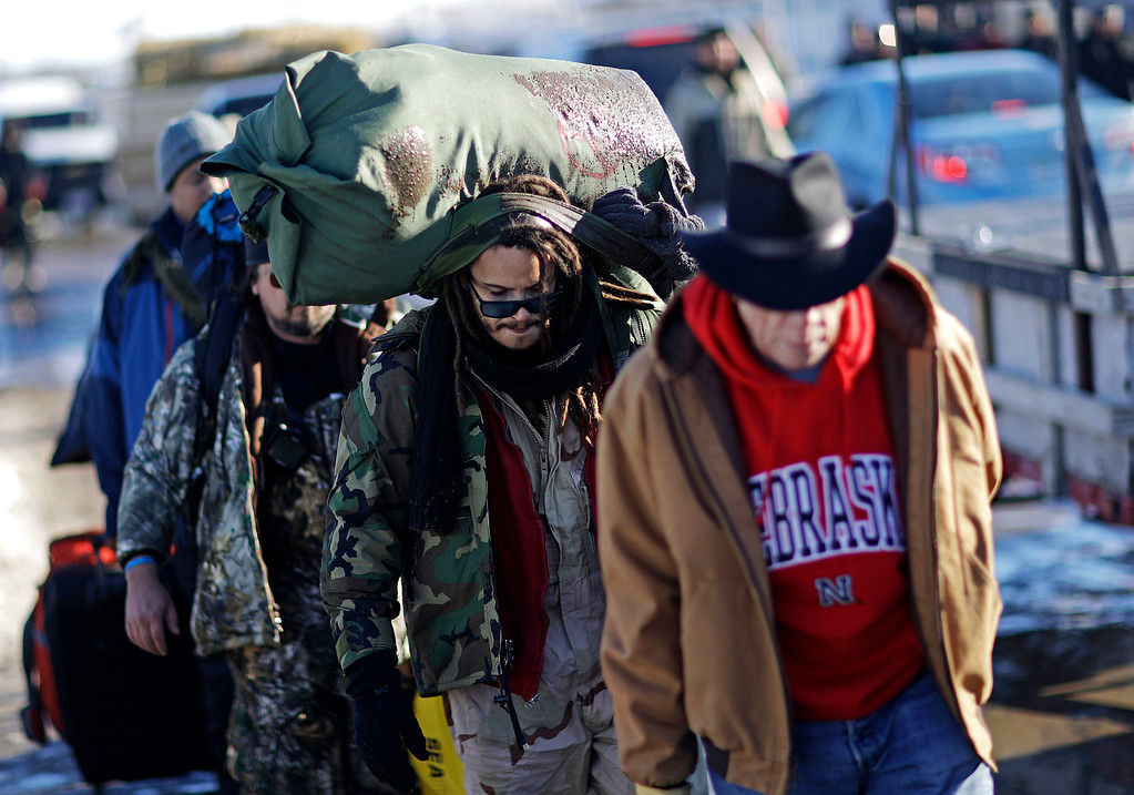 . Marine Corps veteran Nesky Hernandez, center, carries his pack after arriving with fellow veterans at the Oceti Sakowin camp where people have gathered to protest the Dakota Access oil pipeline in Cannon Ball, N.D., Sunday, Dec. 4, 2016. Tribal elders have asked the military veterans joining the large Dakota Access pipeline protest encampment not to have confrontations with law enforcement officials, an organizer with Veterans Stand for Standing Rock said Sunday, adding the group is there to help out those who\'ve dug in against the four-state, $3.8 billion project. (AP Photo/David Goldman)