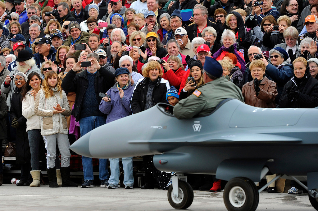 . Parade watchers watch a miniature jet with the US Air Force Total Force Band rolls along the 128th Rose Parade in Pasadena, Calif., Monday, Jan. 2, 2017. The 5½-mile parade featured marching bands, horseback riders and dozens of ornately decorated flower-covered floats. (AP Photo/Michael Owen Baker)