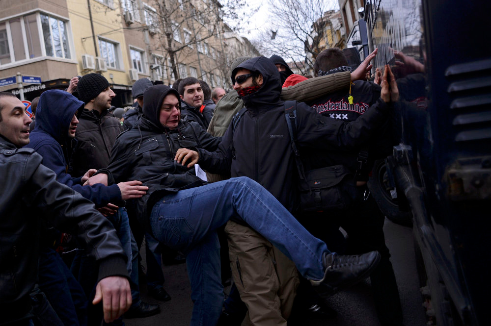 . A man kicks a police van during a protest against high electricity bills in Sofia February 17, 2013. Tens of thousands of Bulgarians protested in more than 20 cities against high electricity bills on Sunday, piling pressure on the government after a week of persistent demonstrations.  REUTERS/Tsvetelina Belutova