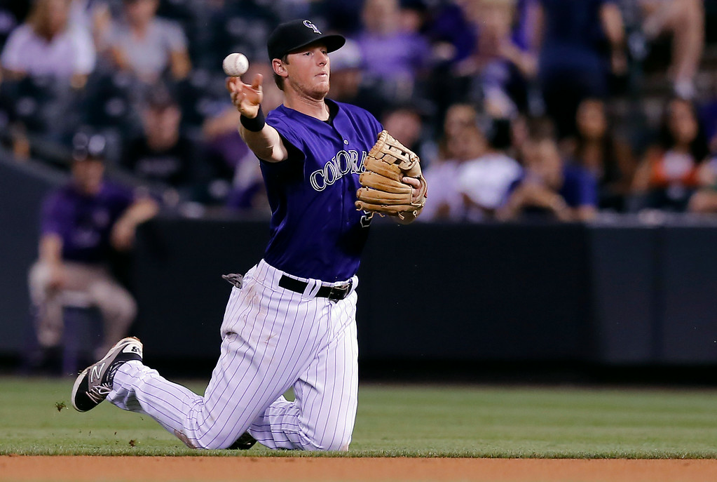 . Colorado Rockies second baseman DJ LeMahieu throws out Joe Panik at first during the fifth inning of a baseball game Tuesday, Sept. 2, 2014, in Denver. (AP Photo/Jack Dempsey)