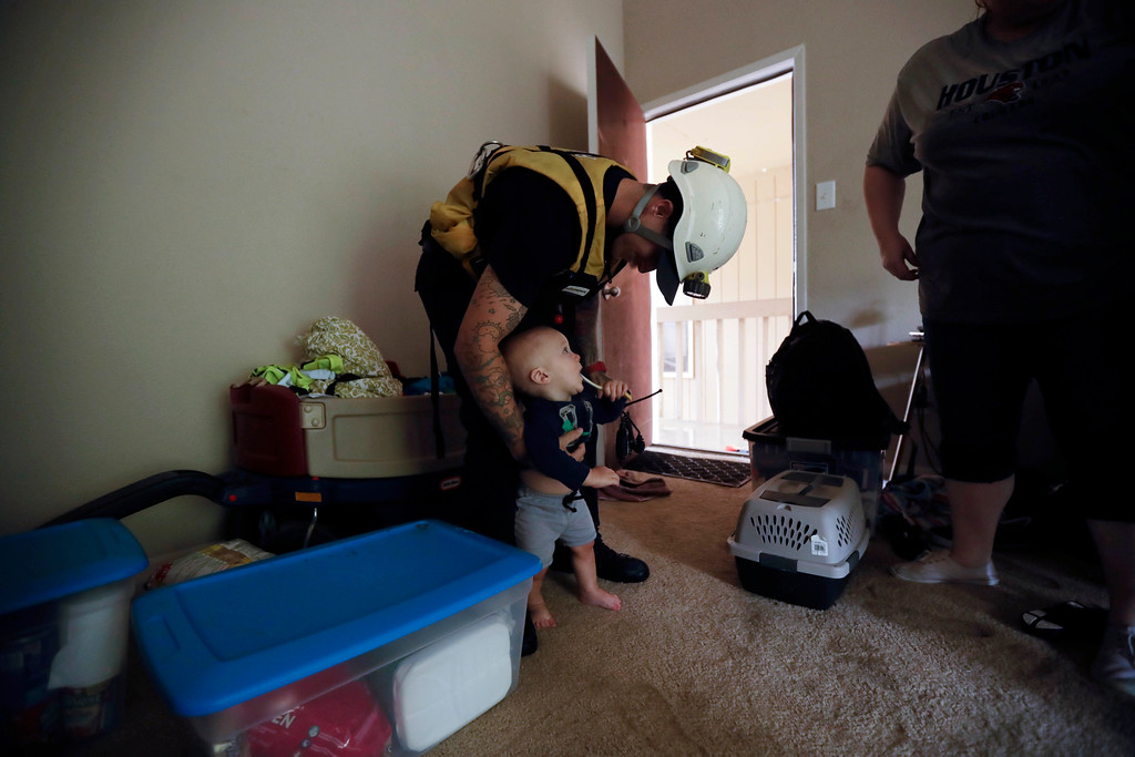 . Steven Sullivan, of Leander Fire Department, greets six-month-old Toby Reznor as he helps rescue the Reznor family from their apartment floodwaters from Tropical Storm Harvey Tuesday, Aug. 29, 2017, in Kingwood, Texas. (AP Photo/Gregory Bull)