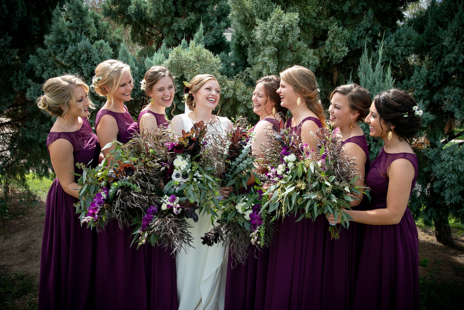 bridesmaids wearing purple dresses holding wildflower bouquets smiling at a brind standing in the middle of them