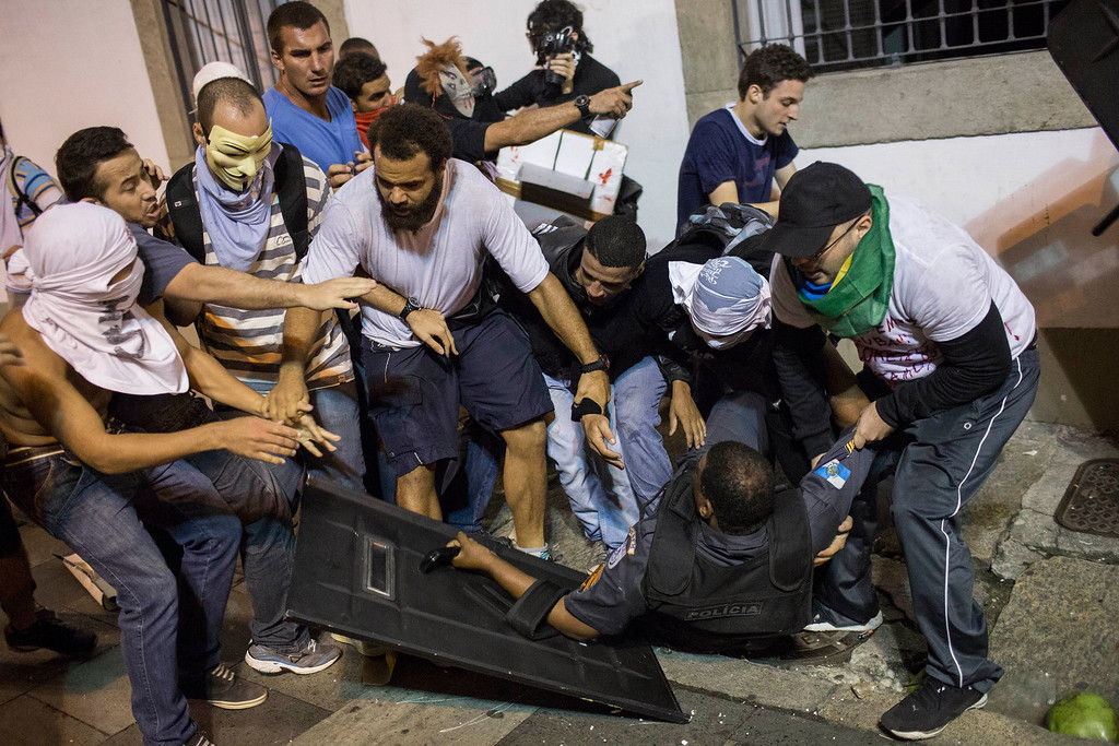 . Protesters try to help a police officer after he clashed with others during a protest in Rio de Janeiro, Brazil, Monday, June 17, 2013. Officers in Rio fired tear gas and rubber bullets when a group of protesters invaded the state legislative assembly and threw rocks and flares at police as protesters massed in at least seven Brazilian cities Monday for another round of demonstrations voicing disgruntlement about life in the country, raising questions about security during big events like the current Confederations Cup and a papal visit next month.  (AP Photo/Felipe Dana)
