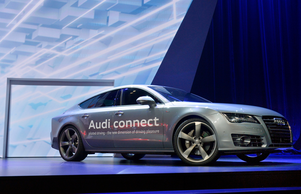 Description of . Audi's autonomous car drives on stage during the Audi keynote at the International Consumer Electronics Show, Monday, Jan. 6, 2014, in Las Vegas. (AP Photo/Jack Dempsey)