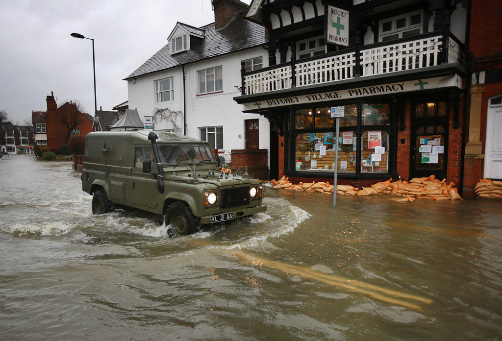 . An Army Landrover drives through flood water in the High Street  on February 12, 2014 in Datchet, England.The Environment Agency contiues to issue severe flood warnings for a number of areas on the river Thames in the commuter belt west of London. With heavier rains forecast for the coming week people are preparing for the water levels to rise.  (Photo by Peter Macdiarmid/Getty Images)