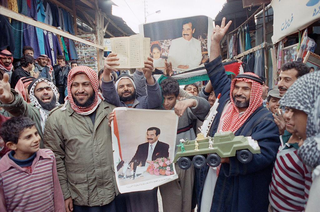. Palestinians celebrate the Iraqi attack on Israel, Jan. 23, 1991, in Baqaa camp.  Man on right holds a toy rocket launcher. Others hold Saddam posters and the Koran. (AP Photo/Ali Mohammed)