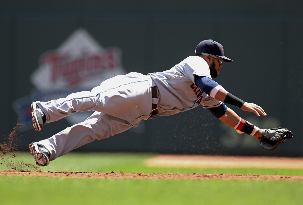 . Cleveland Indians first baseman Carlos Santana makes a futile dive for a sharp grounder as Minnesota Twins\' Danny Santana triples in the third inning of a baseball game, Wednesday, July 23, 2014, in Minneapolis. (AP Photo/Jim Mone)
