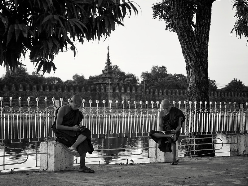 Two monks relaxing by the river in front of the Royal Palace.  Mandalay, Myanmar, 2017.
