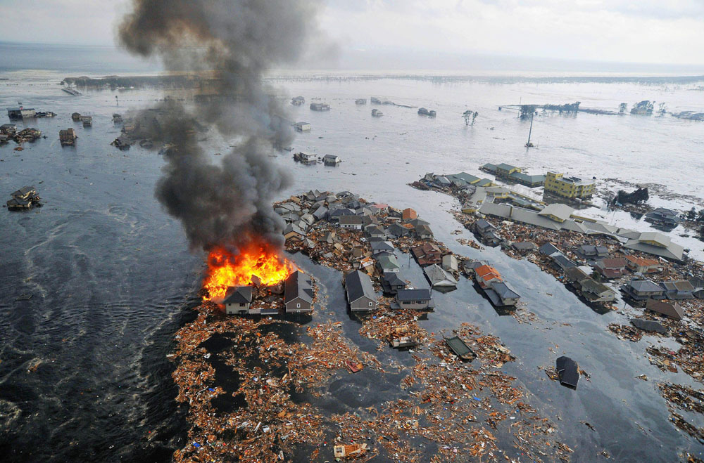 . Houses swallowed by tsunami waves burn in Natori, Miyagi Prefecture (state) after Japan was struck by a strong earthquake off its northeastern coast Friday, March 11, 2011. (AP Photo/Kyodo News)