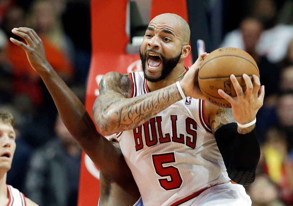 . Chicago Bulls forward Carlos Boozer (5) reacts as he rebounds the ball against Denver Nuggets forward Jordan Hamilton, rear, during the second half of an NBA preseason basketball game in Chicago on Friday, Oct. 25, 2013. The Bulls won 94-89. (AP Photo/Nam Y. Huh)