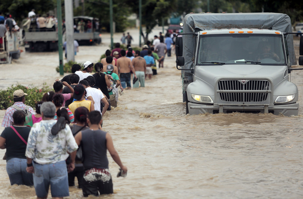 . Residents and tourists wade through a flooded street in Acapulco, Guerrero state, Mexico, on September 17, 2013 as heavy rains hit the country. Mexican authorities scrambled Tuesday to launch an air lift to evacuate tens of thousands of tourists stranded amid floods in the resort of Acapulco following a pair of deadly storms. The official death toll rose to 47 after the tropical storms, Ingrid and Manuel, swarmed large swaths of the country during a three-day holiday weekend, sparking landslides and causing rivers to overflow in several states. Pedro PARDO/AFP/Getty Images