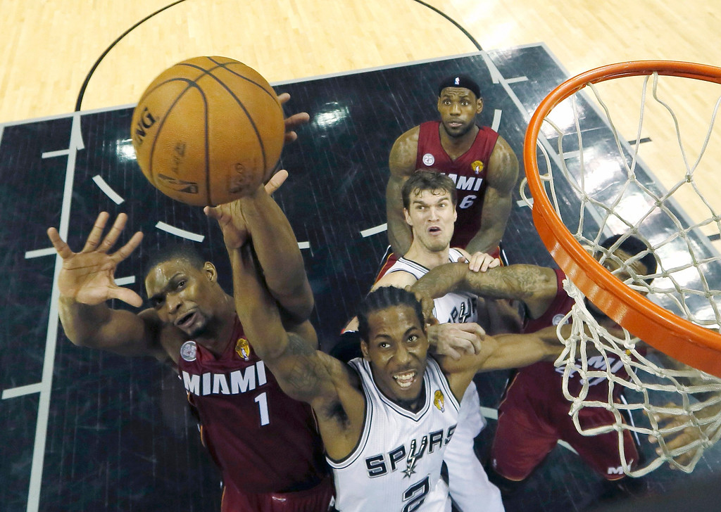 . Miami Heat\'s Chris Bosh (1) goes to the basket against San Antonio Spurs\' Kawhi Leonard (2) during Game 3 of their NBA Finals basketball playoff in San Antonio, Texas June 11, 2013. REUTERS/Mike Ehrmann/Pool