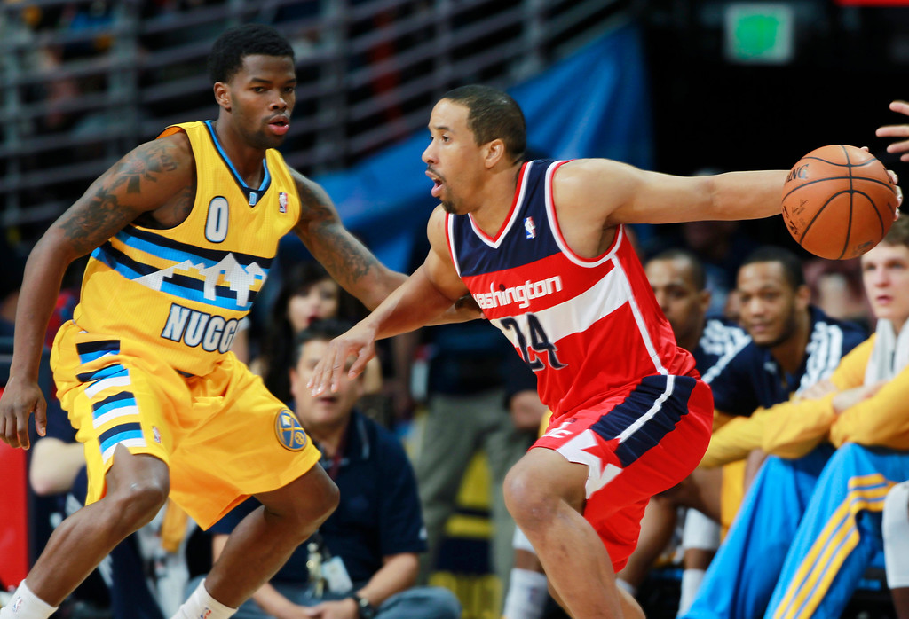 . Washington Wizards guard Andre Miller, right, works ball inside as Denver Nuggets guard Aaron Brooks covers in the fourth quarter of an NBA basketball game in Denver on Sunday, March 23, 2014. The Nuggets won 105-102. (AP Photo/David Zalubowski)