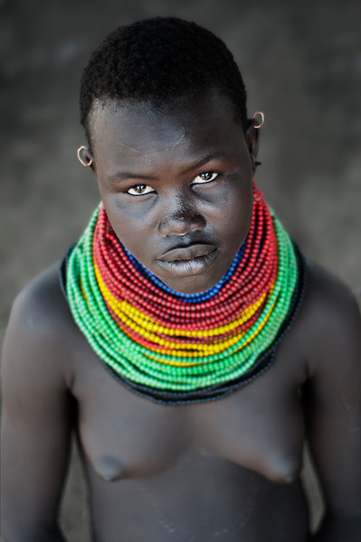 Meet Esinien, a young woman from the Nyangatom tribe. Esinien is still not married and lives with her family on the banks of the Omo River. Although she's still very young, Esinien already boasts a number of scars on her body which she believes make her more attractive. As all Nyangatom women Esinien wears elaborate beads around her neck, the number and color of which convey her social status within the tribe. She enjoys singing, as well as listening to stories told to her by her elders.
