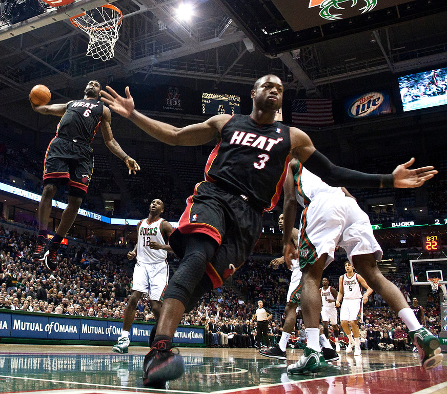 . Miami Heat\'s Dwyane Wade (3) reacts as teammate LeBron James (6) goes up for a dunk during the first half of an NBA basketball game against the Milwaukee Bucks Monday, Dec. 6, 2010, in Milwaukee. (AP Photo/Morry Gash)