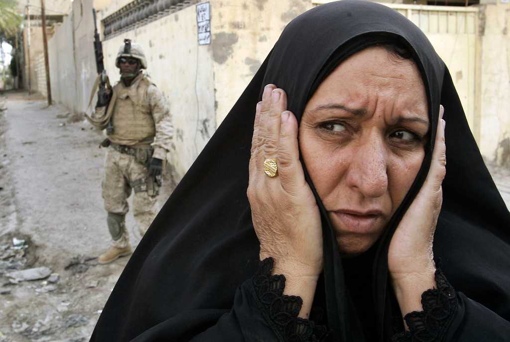 . An Iraqi woman gestures as she tries to flee the fighting in the center of Fallujah, Iraq, Friday, Nov. 12, 2004. (AP Photo/Anja Niedringhaus)
