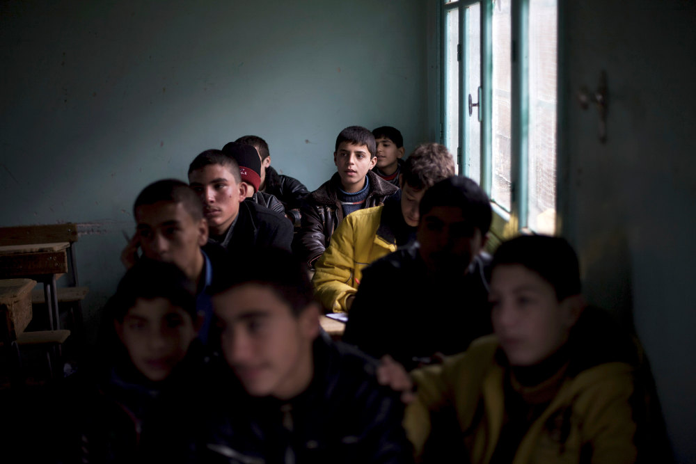 Description of . A Syrian child listens to a lecture in a classroom in a city under control of the Free Syrian Army in Aleppo province, Syria, Thursday, Dec. 13, 2012 (AP Photo/Manu Brabo)