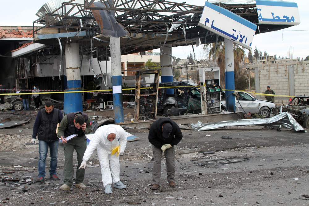 . Lebanese forensic experts gather evidence from the site of a car bomb, that targeted Al-Aytam service station the day before and left at least four people dead, in the town of Hermel, in Lebanon\'s eastern Bekaa valley, on February 2, 2014. The Al-Nusra Front in Lebanon, a group named after Al-Qaeda\'s Syrian affiliate, claimed the attack on Twitter, saying it was a suicide bombing in response to Hezbollah\'s involvement in Syria. (AFP/Getty Images)