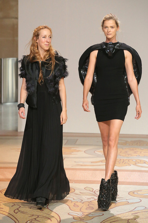 . Dutch designer Iris van Herpen, left, escorted by a model acknowledges applause at the end of her Haute Couture Fall-Winter 2013-2014 collection, Monday, July 1, 2013 in Paris.  (AP Photo/Michel Euler)