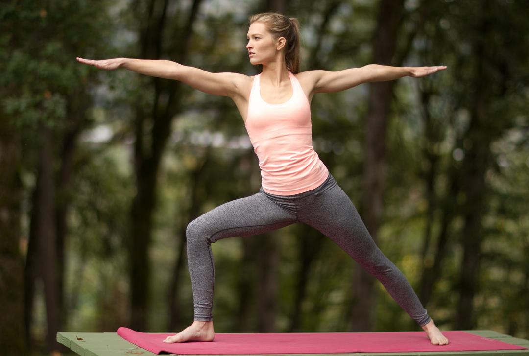 fitness model doing warrior pose in park