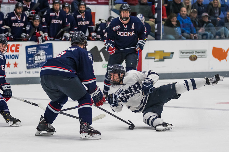 New Hampshire's Eric Esposito (12) has his shot blocked by Connecticut's Adam Karashik (3) during Hockey East action in Durham Saturday. [Scott Patterson/Fosters.com]
