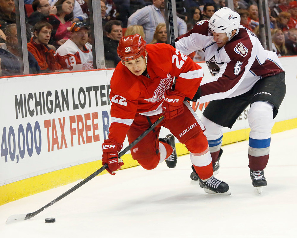 . Detroit Red Wings right wing Jordin Tootoo (22) tries to maintain control of the puck against Colorado Avalanche defenseman Erik Johnson (6) in the second period of an NHL hockey game Monday, April 1, 2013, in Detroit. (AP Photo/Duane Burleson)