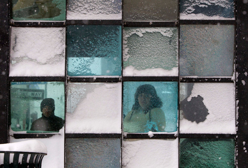 . Riders wait in a bus stop where color-tinted windows collect snow during a storm, Friday, Feb. 8, 2013, in Portland, Maine. The National Weather Service says a blizzard warning is issued Friday evening for the southern coast. The forecast calls for up to 2 feet of snow and winds gusting to 50 mph.(AP Photo/Robert F. Bukaty)